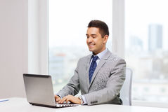 Happy businessman working with laptop in office Royalty Free Stock Image
