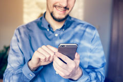Happy businessman working on the smartphone. Royalty Free Stock Photography