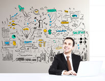 Happy businessman at workplace. Happy young businessman using laptop at bright workplace with business sketch. Success concept Stock Photos