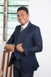 Happy businessman. Young businessman standing in his office and smiling Stock Images