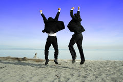 Happy businessmen. Two businessmen jumping and celebrating on the beach