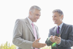 Happy businessmen discussing over mobile phone outdoors Stock Photo