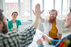 Happy business team. Happy businessmen giving five to each other during a meeting Royalty Free Stock Photos