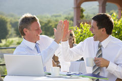 Happy businessmen giving high five and drinking coffee at caf? Stock Photos