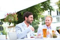 Happy businessmen having food at sidewalk cafe Stock Photo