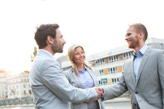 Happy businessmen shaking hands in city against clear sky Royalty Free Stock Photo