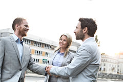 Happy businessmen shaking hands in city against clear sky Royalty Free Stock Photos