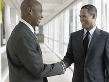Happy Businessmen Shaking Hands In Office Corridor Royalty Free Stock Images
