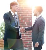 Businessmen shaking hands while standing in office corridor Stock Photography