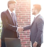 Businessmen shaking hands while standing in office corridor Stock Photos