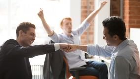 Happy businessmen workers giving fist bump celebrating team project success. Congratulating with corporate victory, rejoicing business win or reward stock photos