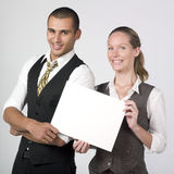 Happy businesspeolpe holding blank notice. A portrait of two happy businesspeolpe holding a blank notice stock image