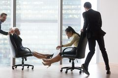 Businesspeople having fun riding on chairs and laughing in offic Stock Image