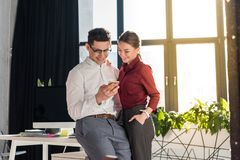 happy businesspeople couple at modern office using royalty free stock images