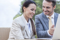 Happy businesspeople discussing over laptop outdoors Stock Photography