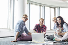 Happy businesspeople looking away while working on floor at creative office Royalty Free Stock Photography
