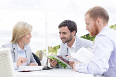 Happy businesspeople reading menu at sidewalk cafe Royalty Free Stock Image