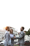 Happy businesspeople shaking hands in city against clear sky Royalty Free Stock Image