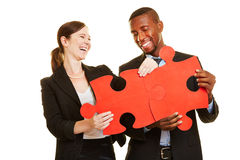 Happy businesspeople solving jigsaw puzzle Stock Image