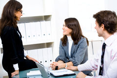 Happy businesspeople talking at office. Young happy businesspeople talking at office, two sitting on chairs one sitting on table stock photo