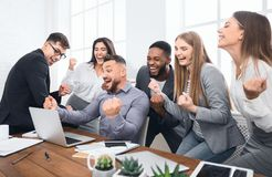 Happy businesspeople triumphing with raised fists in office stock photo