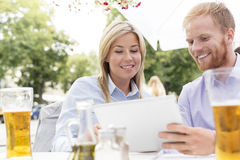 Happy businesspeople using digital tablet at sidewalk cafe Royalty Free Stock Photos