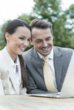 Happy businesspeople using laptop outdoors Royalty Free Stock Images