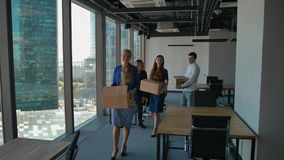 Happy businesspeople walk in new office, with boxes, smiling.