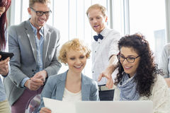 Happy businesspeople working on laptop in creative office Stock Photography
