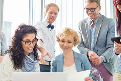 Happy businesspeople working on laptop in creative office stock photos