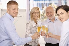 Happy businessteam celebrating. With glasses of champagne, smiling at camera Stock Image
