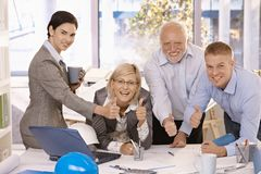 Happy businessteam giving thumbs up at work. Portrait of happy businessteam giving thumbs up at work, smiling at camera Royalty Free Stock Photo