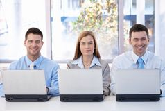 Happy businessteam working on individual laptops. Happy team of young businesspeople working on individual laptops stock image