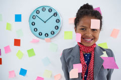 Happy businesswoman with adhesive notes stuck on suit and head Stock Image