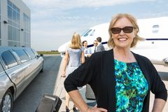 Happy Businesswoman Against Private Jet. Portrait of happy mature businesswoman with limousine and private jet in background Stock Photos