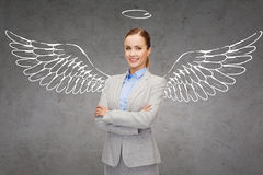Happy businesswoman with angel wings and nimbus Stock Photo