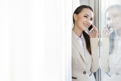 Happy businesswoman answering cell phone in office Royalty Free Stock Photos