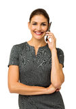 Happy Businesswoman Answering Smart Phone. Portrait of happy businesswoman answering smart phone against white background. Vertical shot Stock Images