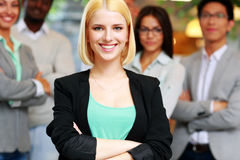 Happy businesswoman with arms folded standing Stock Images