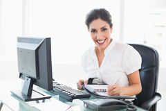 Happy businesswoman arranging her diary at her desk Royalty Free Stock Photo