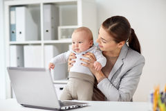 Happy businesswoman with baby and laptop at office Stock Photos