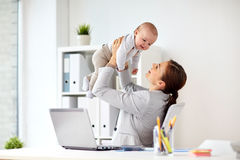 Happy businesswoman with baby and laptop at office Stock Images