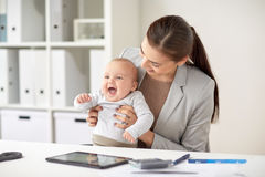 Happy businesswoman with baby working at office Stock Photo