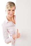 Happy businesswoman behind empty banner thumbs up Stock Photography