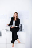 Happy Businesswoman With Binder Sitting On Counter Royalty Free Stock Photo