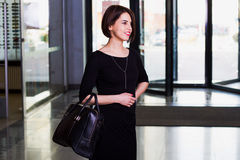 Happy businesswoman in black dress walking with briefcase in sh. Handsome and Royalty Free Stock Images