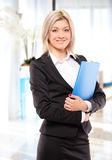 A happy businesswoman with blue folder. Posing in the office stock images