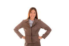 Happy businesswoman in brown suit is smiling and arms akimbo on Stock Images