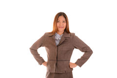 Happy businesswoman in brown suit is smiling and arms akimbo on Royalty Free Stock Photo