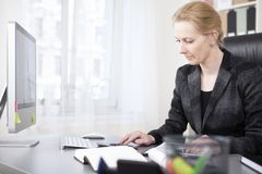 Happy Businesswoman Calculating at her Worktable Stock Images